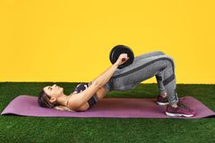 Handsome fit young woman do exercise with dumbbells on the fitness purple mat on green grass over yellow background. Handsome fit young woman do exercise with royalty free stock image