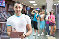 Handsome fitness instructor. Smiling young fitness instructor making note with gym girls in background Stock Images