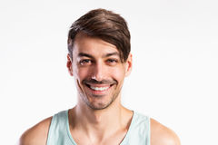 Handsome fitness man in blue tank top shirt, studio shot. Royalty Free Stock Photo
