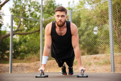 Handsome fitness man doing push-up exercises with sport equipment. Handsome young fitness man doing push-up exercises with sport equipment outdoors Royalty Free Stock Photography
