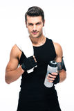Handsome fitness man holding towel and bottle with water. Isolated on a white background. Looking at camera royalty free stock photos