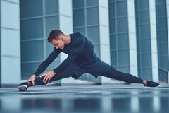 A handsome fitness man in a sportswear, doing stretching while preparing for serious exercise in the modern city against. A skyscraper. Healthy lifestyle Stock Images