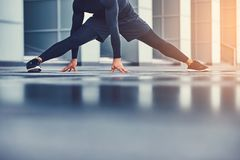 A handsome fitness man in a sportswear, doing stretching while preparing for serious exercise in the modern city against. A skyscraper. Healthy lifestyle Royalty Free Stock Photos