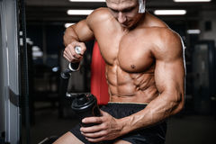 Handsome fitness model holding a shaker in the gym gain muscle. Healthcare lifestyle sexy caucasian man bodybuilder work out naked body Royalty Free Stock Images