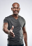 Handsome fitness trainer reaching to shake hands. Single handsome young Black male fitness trainer in gray compression shirt reaching out toward camera to shake Stock Photos
