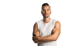 Handsome fitness trainer. Well trained and attractive man wearing a white tank top standing against a white background with his arms crossed Stock Image