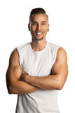 Handsome fitness trainer. Well trained and attractive man wearing a white tank top standing against a white background with his arms crossed Stock Images