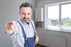 Handsome fitter pointing finger at you. Handsome fitter with steel wrench pointing finger at you in the house with copy space Royalty Free Stock Photo