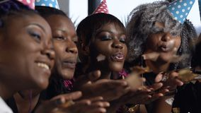 Handsome five african women blowing golden confetti on the birthday party. Portrait of handsome five african women in colorful hat blowing golden confetti on stock video footage