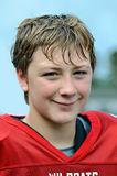 Handsome Football Player. A preteen football player smiling during a break in the game stock photo