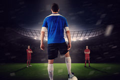 Handsome football player in blue jersey facing opposition Stock Photography