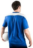 Handsome football player holding the ball Stock Image