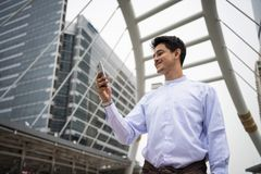 Handsome foreign Businessman in town. Portrait of Handsome Burmese or Myanmar businessman with longyi traditional dress using smart or mobile phone in Bangkok Royalty Free Stock Photography