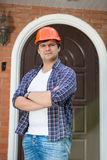 Handsome foreman in hardhat posing against new built house Royalty Free Stock Images