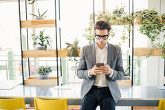Handsome freelance business man sitting on table with phone in hands and typing message in office Stock Image