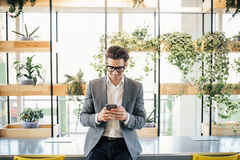Handsome freelance business man sitting on table with phone in hands and typing message in office Stock Photo