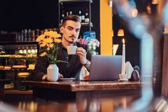 Handsome freelancer man with stylish beard and hair dressed in a black suit sitting at a cafe with an open laptop and. Holds a cup of coffee, looking at a royalty free stock images