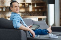Handsome freelancer posing on camera. Just a second. Relaxed man keeping smile on his face and turning head while holding his tablet in right hand Stock Photos