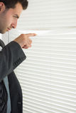 Handsome frowning businessman spying through roller blind Royalty Free Stock Photos