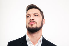 Handsome frowning young businessman with beard looking away Stock Photos