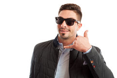 Handsome and funky sales man making call me gesture. Handsome and funky sales man making call me or contact us gesture with the hand royalty free stock photography
