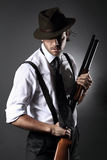 Handsome gangster posing with shotgun and hat Stock Image