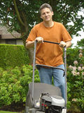 Handsome gardener. Man pushing a gas powered lawn mower Royalty Free Stock Photography