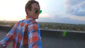 Handsome gay holds hand of his boyfriend and runs to edge of roof to admire view. Follow me shot of young man pull his. Lover on rooftop. Beautiful landscape at stock video footage