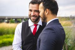 A Handsome gay male couple in the park on their wedding day. Handsome gay male couple in the park on their wedding day royalty free stock image