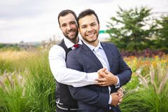 A Handsome gay male couple in the park on their wedding day. Handsome gay male couple in the park on their wedding day royalty free stock photography