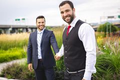 A Handsome gay male couple in the park on their wedding day. Handsome gay male couple in the park on their wedding day stock photo