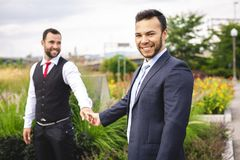 A Handsome gay male couple in the park on their wedding day. Handsome gay male couple in the park on their wedding day stock photos