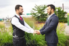 A Handsome gay male couple in the park on their wedding day. Handsome gay male couple in the park on their wedding day royalty free stock photo