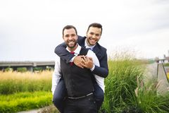A Handsome gay male couple in the park on their wedding day. Handsome gay male couple in the park on their wedding day stock image