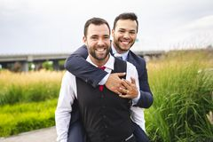 A Handsome gay male couple in the park on their wedding day. Handsome gay male couple in the park on their wedding day stock photography