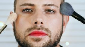Handsome gay or metrosexual man getting makeup. Closeup portrait of attractive bearded metrosexual or gay man getting makeup with brushes from two sides stock video