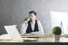 Handsome gentleman drinking coffee at workplace Royalty Free Stock Photos