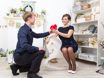 Handsome gentleman presents heart to his beautiful lady on white Stock Images