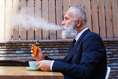 Handsome gentleman smoking electrocigarette over a cup of coffee. Mid shot of handsome gentleman smoking electrocigarette over a cup of coffee while sitting Stock Images