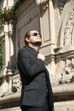 Handsome gentleman in a suit enjoying the sun - architectonic background.  stock images