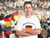 Handsome german fan with dark hair with other fans. In the background Stock Photography