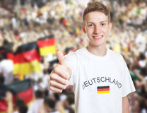 Handsome german fan showing thumb with other fans Royalty Free Stock Photography