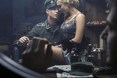 Handsome german soldier with blonde woman on his knees Stock Photos