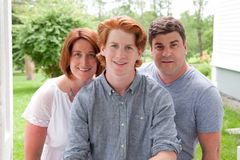 Proud parents with son. A handsome ginger red head boy with his proud smiling parents royalty free stock photography