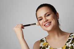 Handsome girl with black fixed hair behind, dark big eyes, thick eyebrows and summer dress doing make up.Model with stock photography