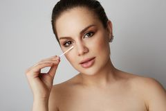 Handsome girl refreshing skin face with white cotton buds over gray studio background.Model with light nude make-up. Healthcare skin makeup concept stock photos
