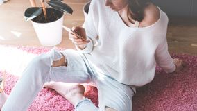 Handsome girl sitting on pink carpet on the floor at modern light coloured living room and typing hand on mobile phone. Handsome girl sitting on pink carpet on Stock Photos