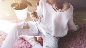 Handsome girl sitting on pink carpet on the floor at modern light coloured living room and using smartphone. Handsome girl sitting on pink carpet on the floor Royalty Free Stock Photo