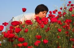 Handsome girl smells poppies. Greece, Halkidiki Stock Image