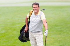 Handsome golfer standing with golf bag Stock Photography